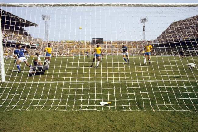 Italy's Paolo Rossi (l) slides the ball past Brazil goalkeeper Waldir Peres (second l) to score the winning goal as Brazil's Junior (third l), Luisinho (third r) and Oscar (r), and Italy's Francesco Graziani (second r), look on