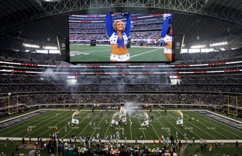 A member of the Dallas Cowboys cheerleaders is seen on the video screen at Cowboys Stadium during introductions before an NFL football game against the Miami Dolphins Thursday, Nov. 24, 2011, in Arlington, Texas. (AP Photo/Matt Strasen )